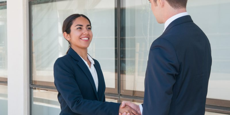 Smiling Ambitious Business Woman Saying Good Bye To Partner. Young Man And Woman In Formal Suits Shaking Hands. Business Handshake Concept