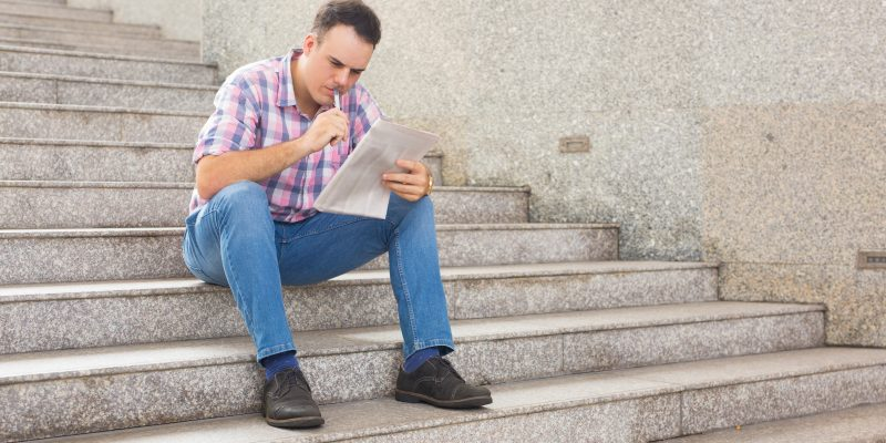Serious Thoughtful Young Man Searching For Job In Newspaper. Pensive Guy In Casual Clothing Sitting On Stairs And Seeking Employment Or Doing Crossword Outdoors. Finding Job Concept